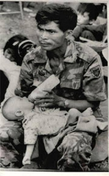 An RVN soldier feeding a baby